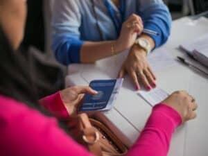 Imagem de duas pessoas em uma sala, uma delas está com sua carteira de trabalho. A imagem representa o conteúdo sobre calculadora FGTS.