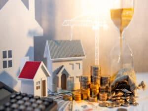 calculadora, maquete de casinhas, moedas e uma ampulheta