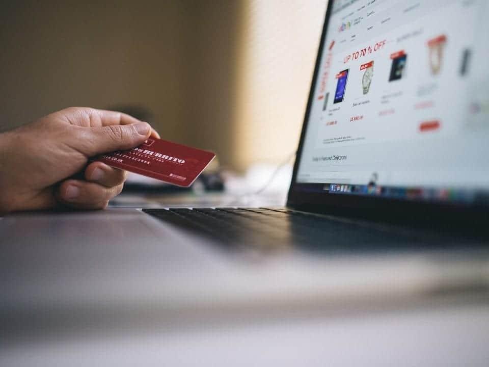 Imagem de uma pessoa usando o computador para entender se o cartão de milhas ou cashback valem a pena