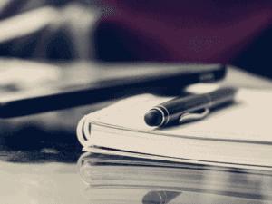 caderno com caneta, representando cartilha sobre open banking