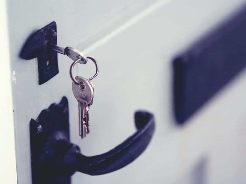 Imagem de uma chave na porta de casa, representando a notícia em que o casa verde amarela e suas diferenças entre o MCMV são expostas