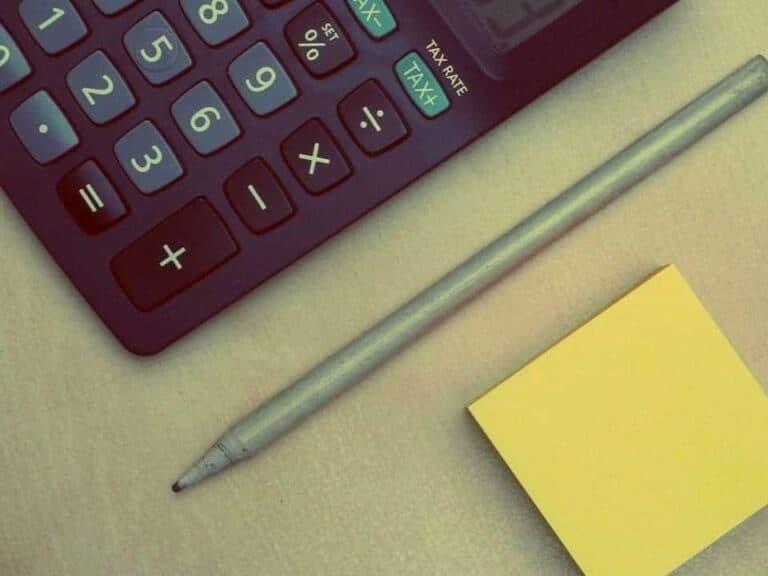 imagem que mostra uma calculadora e um lápis para ilustrar como calcular juros de financiamento