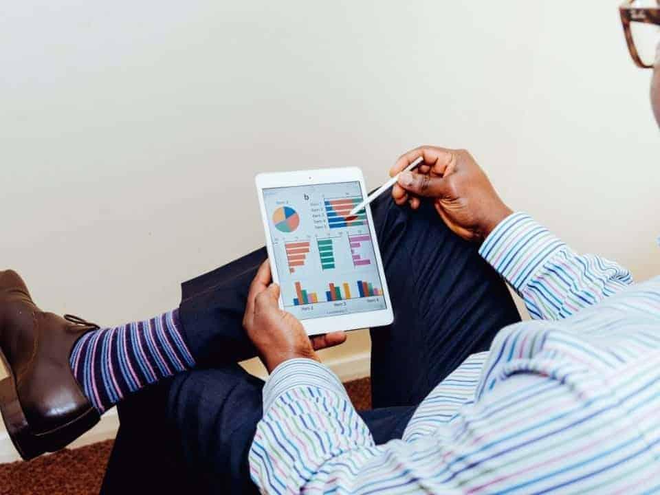 Imagem de um homem usando um tablet para aprender como investir em fundos imobiliários