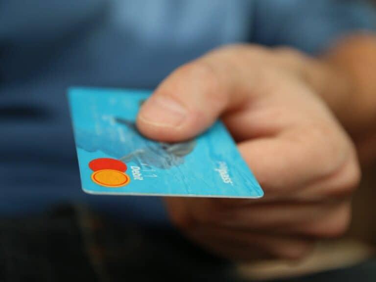 Imagem de uma pessoa mostrando um cartão, representando o conteúdo sobre como ter cartão de crédito aprovado na hora