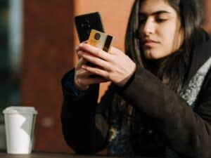 mulher olha para o celular enquanto está sentada em uma mesa. em uma das mãos, ela segura um cartão de crédito. a imagem representa como reduzir os gastos com compras online