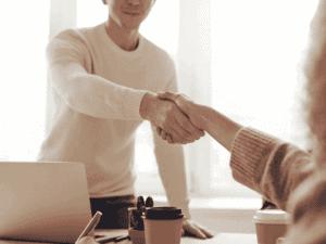 duas pessoas estão de lados opostos de uma mesa. elas apertam as mãos, simbolizando a chance de conseguir um emprego na crise