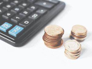 moedas e calculadora, representando estimativa para inflação