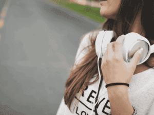 mulher com fone de ouvido, representando investir em direitos musicais