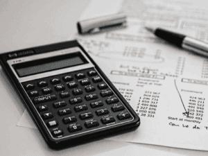 calculadora e papéis, representando investir o dinheiro da rescisão