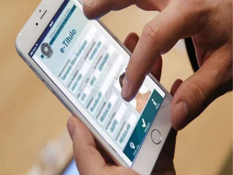 close de mão e celular, representando justificar voto pelo celular