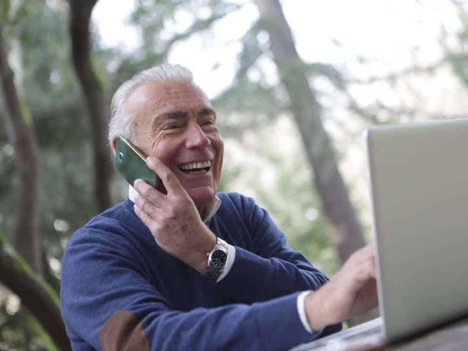 Imagem de um senhor usando o computador para ver a notícia sobre o limite do cartão Caixa Simples