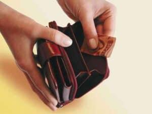 mãos abrindo uma carteira e tirando uma nota de 50 reais dobrada