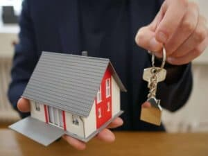 Imagem de uma casa de miniatura com chaves para representar o conteúdo sobre o novo leilão de imóveis do Santander
