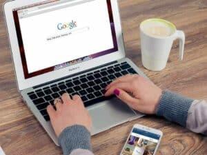 mãos de mulher fazendo busca no Google em notebook representando vagas de emprego no mercado financeiro
