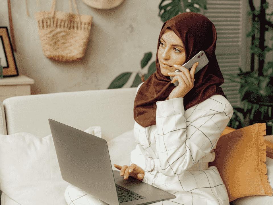 mulher com notebook e celular, simbolizando parceria para cashback