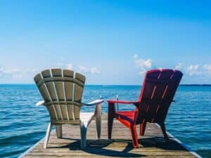 duas cadeiras de frente para o mar representando a aposentadoria após a previdência privada valer a pena