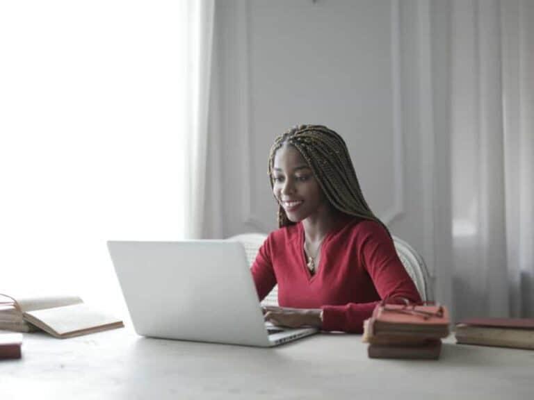 Imagem de uma mulher usando o computador para saber mais sobre o programa para substituir GRU