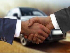 aperto de mãos em frente a carro, representando renegociação de financiamento de carros