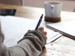 Imagem de uma pessoa escrevendo em um papel com uma lapiseira, representando o conteúdo em que renegociação de dívidas na pandemia