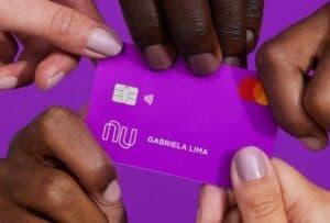 Imagem de um cartão roxo com várias mãos o segurando, representando a notícia sobre o resgate planejado do Nubank