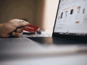 pessoa com cartão de crédito e computador, representando semana do brasil