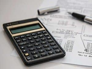 Imagem de uma calculadora e papéis simbolizando o conteúdo sobre simulador de financiamento
