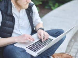 Imagem de um homem usando o computador para descobrir os melhores sites para ganhar dinheiro na internet