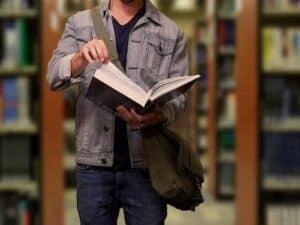 close em mãos folheando livro em biblioteca representando vagas remanescentes do Prouni