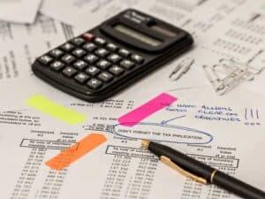 folha com vários números escritos, uma calculadora e uma caneta em cima demonstrando os impostos a serem pagos, como a taxa de carregamento