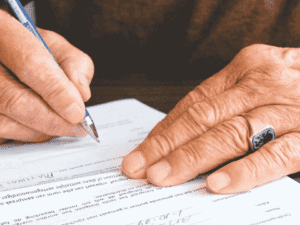 homem assinando papel, representando taxas de juros em empréstimo pessoal