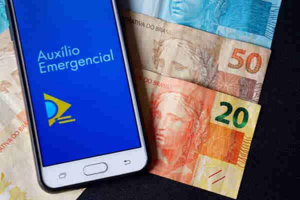 celular com aplicativo do auxílio emergencial e cédulas de real, representando 2ª parcela do auxílio residual