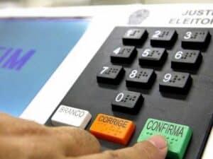 dedo aperta botão Confirma da urna eletrônica representando Aplicativos para Eleições 2020