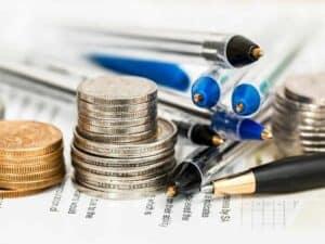 pilhas de moedas, papéis e canetas representando Banco do Brasil e UBS