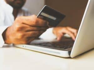 Homem vendo dados do cartão de crédito para realizar uma compra online, representando Black Friday 2020