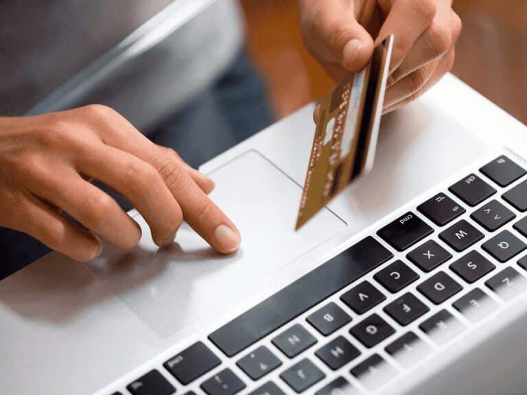 pessoa com cartão e computador, representando Como não cair em golpes na Black Friday
