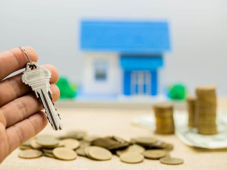 Chave, moedas e maquete de casa ao fundo representando Feirão da Caixa online