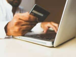pessoa olhando cartão de crédito para fazer compra online via notebook representando Google Shopping na Black Friday