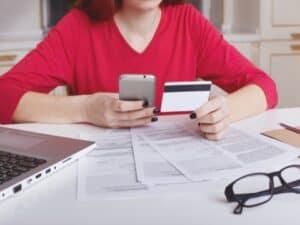 Mulher analisa juros do rotativo do cartão e cheque especial