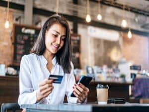 mulher paga com cartão de crédito via smartphone representando Oi e TIM fecham parceria com a Quod