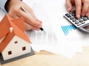 Cálculos sendo realizados em um documento com o auxílio de uma calculadora. Há uma maquete de casa sobre a mesa. Imagem representando Reajuste no aluguel.
