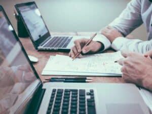 Mesa com notebooks e o que parece um contrato, sendo lido por duas pessoas. Uma delas está com uma caneta em mãos, prestes a assiná-lo. Imagem representando Redução nos juros do financiamento imobiliário.
