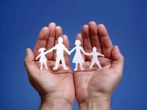 mão com origami de família, representando Seguro de vida e acidentes pessoais
