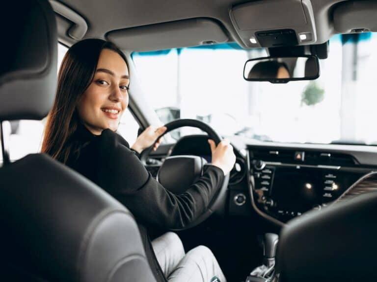 Mulher dirigindo carro representando Uber volta a contratar