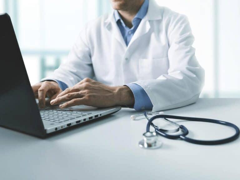 médico em computador, representando atendimento médico online gratuito