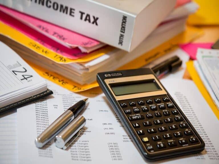 papéis, agenda, pastas, canetas e calculadora em cima da mesa representando alíquota de 17% do compulsório sobre recursos a prazo