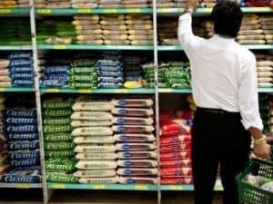 Homem pegando um arroz no supermercado, simbolizando produto que teve a tarifa de importação zerada.