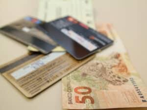 cédula de real e cartões, representando bancarização na pandemia