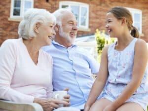 Casal de idosos com sua neta, sorridentes, representando calcular a aposentadoria