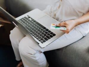 Imagem de uma mulher fazendo compras online no cartão de crédito para ilustrar o conteúdo sobre cartão de crédito com limite alto
