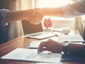 aperto de mãos entre sócios que aprenderam como abrir uma empresa de prestação de serviços
